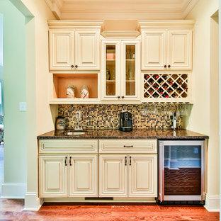 アトランタの小さいトラディショナルスタイルのおしゃれなウェット バー (I型、アンダーカウンターシンク、レイズドパネル扉のキャビネット、白いキャビネット、御影石カウンター、マルチカラーのキッチンパネル、モザイクタイルのキッチンパネル、淡色無垢フローリング、茶色い床) の写真