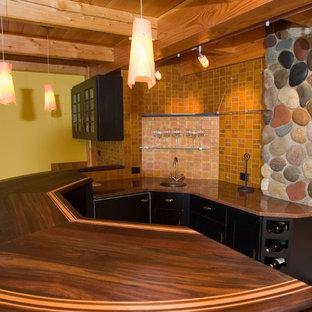 ニューヨークの中くらいのおしゃれな着席型バー (コの字型、アンダーカウンターシンク、フラットパネル扉のキャビネット、黒いキャビネット、木材カウンター、茶色いキッチンパネル、ガラスタイルのキッチンパネル、無垢フローリング、茶色い床、オレンジのキッチンカウンター) の写真