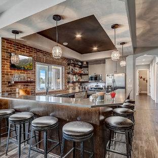 ミルウォーキーの巨大なビーチスタイルのおしゃれな着席型バー (アンダーカウンターシンク、フラットパネル扉のキャビネット、グレーのキャビネット、クオーツストーンカウンター、茶色いキッチンパネル、レンガのキッチンパネル、マルチカラーの床、グレーのキッチンカウンター) の写真