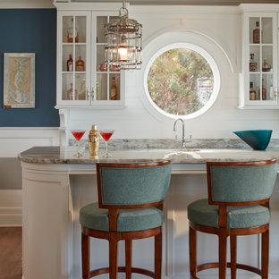 Esempio di un bancone bar costiero con lavello integrato, ante di vetro, ante bianche, paraspruzzi bianco, paraspruzzi in perlinato, pavimento in legno massello medio, pavimento marrone e top grigio
