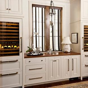 バーミングハムのトラディショナルスタイルのおしゃれなウェット バー (ドロップインシンク、インセット扉のキャビネット、木材カウンター、濃色無垢フローリング、I型、白いキャビネット、茶色いキッチンカウンター) の写真