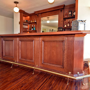 Foto di un angolo bar vittoriano di medie dimensioni con consolle stile comò, ante rosse, top in legno, paraspruzzi in legno, parquet scuro, pavimento giallo e top rosso