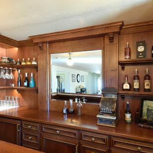 Cette photo montre un bar de salon victorien de taille moyenne avec un placard en trompe-l'oeil, des portes de placard rouges, un plan de travail en bois, une crédence en bois, un sol en bois foncé, un sol jaune et un plan de travail rouge.