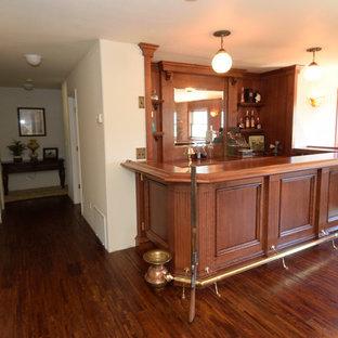 Idee per un angolo bar vittoriano di medie dimensioni con consolle stile comò, ante rosse, top in legno, paraspruzzi in legno, parquet scuro, pavimento giallo e top rosso