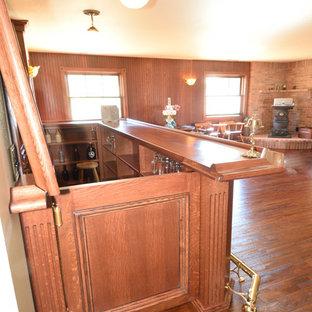 他の地域の中くらいのヴィクトリアン調のおしゃれなホームバー (家具調キャビネット、赤いキャビネット、木材カウンター、木材のキッチンパネル、濃色無垢フローリング、黄色い床、赤いキッチンカウンター) の写真