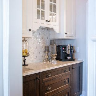 ミルウォーキーの広いビーチスタイルのおしゃれなホームバー (ll型、家具調キャビネット、濃色木目調キャビネット、ライムストーンカウンター、マルチカラーのキッチンパネル、モザイクタイルのキッチンパネル、濃色無垢フローリング、ベージュのキッチンカウンター) の写真