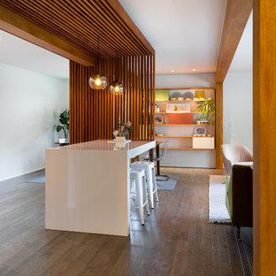 Idee per un bancone bar minimalista di medie dimensioni con nessun lavello, ante lisce, ante in legno scuro, top in laminato, paraspruzzi bianco, parquet scuro e pavimento marrone