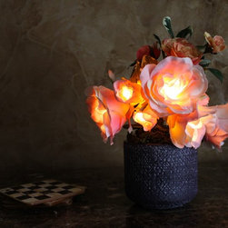 The Firefly Garden - Radiant Roses - Pink/Peach in Purple Ceramic Vase - Bring the timeless beauty of Roses to your home, with the added feature of lighting. Housed in a selection of vases, Radiant Roses is perfect for a guest bedroom or bathroom. This battery operated floral arrangement is a unique alternative to a night light .The glowing Roses cast subtle and beautiful shadows to accent any space.