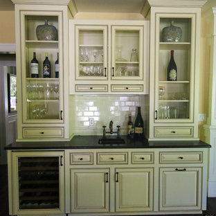 Photo of a medium sized classic single-wall wet bar in Portland with a submerged sink, raised-panel cabinets, white cabinets, composite countertops, white splashback and metro tiled splashback.
