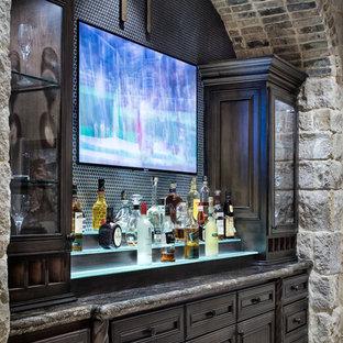 Cette image montre un très grand bar de salon linéaire méditerranéen avec un placard à porte vitrée et des portes de placard en bois sombre.