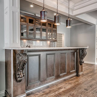 Inspiration for a country galley wet bar in Oklahoma City with glass-front cabinets, dark wood cabinets, marble worktops, marble splashback and medium hardwood flooring.