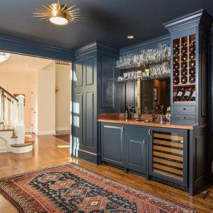 Foto di un angolo bar con lavandino tradizionale con lavello da incasso, ante con bugna sagomata, ante blu, top in legno, parquet scuro e top marrone