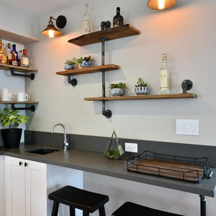 Wet bar - mid-sized industrial l-shaped light wood floor and brown floor wet bar idea in San Diego with shaker cabinets, white cabinets, quartz countertops, an undermount sink and gray backsplash