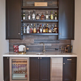 This is an example of a medium sized classic single-wall wet bar in San Diego with a submerged sink, shaker cabinets, black cabinets, marble worktops, brown splashback, ceramic splashback and light hardwood flooring.