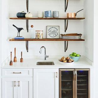 Modelo de bar en casa con fregadero lineal, marinero, con fregadero bajoencimera, armarios estilo shaker, puertas de armario blancas, salpicadero blanco, suelo de madera en tonos medios y encimeras blancas