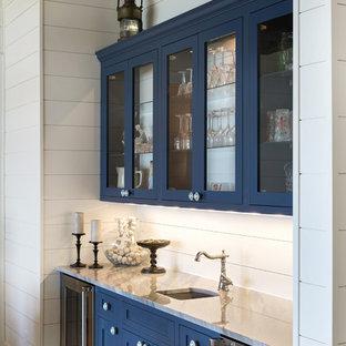 Diseño de bar en casa con fregadero lineal, marinero, con fregadero bajoencimera, puertas de armario azules, encimera de mármol, salpicadero blanco, salpicadero de madera, suelo marrón, armarios tipo vitrina y suelo de madera oscura