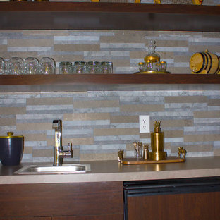 Inspiration for a small contemporary single-wall limestone floor wet bar remodel in Detroit with a drop-in sink, flat-panel cabinets, dark wood cabinets, granite countertops, multicolored backsplash and stone tile backsplash