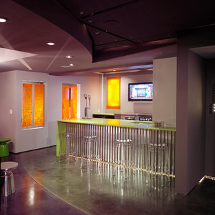 ニューヨークの広いコンテンポラリースタイルのおしゃれな着席型バー (グレーの床、アンダーカウンターシンク、ラミネートカウンター、コンクリートの床、緑のキッチンカウンター) の写真