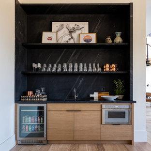 ソルトレイクシティのラスティックスタイルのおしゃれなウェット バー (I型、アンダーカウンターシンク、フラットパネル扉のキャビネット、淡色木目調キャビネット、黒いキッチンパネル、淡色無垢フローリング、ベージュの床、黒いキッチンカウンター) の写真