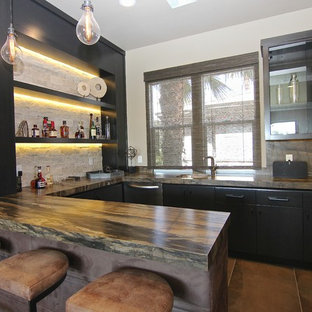 Example of a large classic u-shaped limestone floor wet bar design in Las Vegas with an undermount sink, flat-panel cabinets, gray cabinets, granite countertops, beige backsplash and stone tile backsplash