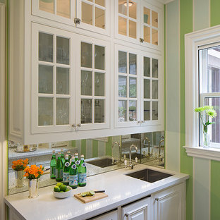 Photo of a small classic wet bar in Denver with a submerged sink, glass-front cabinets, white cabinets, mirror splashback and white worktops.