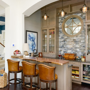 Ispirazione per un bancone bar costiero con ante di vetro, ante marroni, paraspruzzi multicolore, parquet scuro e pavimento marrone