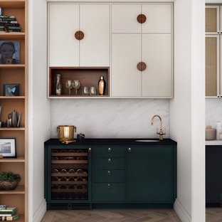 Design ideas for a small modern home bar in Toronto with a submerged sink, flat-panel cabinets, white cabinets, engineered stone countertops, white splashback, marble splashback, medium hardwood flooring, brown floors and black worktops.