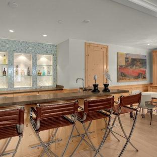 Foto di un bancone bar contemporaneo con lavello da incasso, nessun'anta, ante in legno scuro, top in cemento, paraspruzzi blu, paraspruzzi con piastrelle di vetro, parquet chiaro, pavimento beige e top marrone