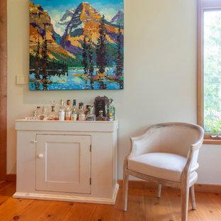 モントリオールの小さいラスティックスタイルのおしゃれなバーカート (I型、家具調キャビネット、白いキャビネット、木材カウンター、無垢フローリング、オレンジの床、白いキッチンカウンター) の写真