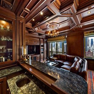 Idee per un grande bancone bar chic con ante di vetro, ante in legno scuro, top in granito, pavimento in laminato, pavimento giallo, top grigio e lavello sottopiano