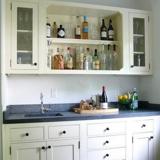 ブリッジポートの小さいトラディショナルスタイルのおしゃれなウェット バー (ll型、一体型シンク、家具調キャビネット、ベージュのキャビネット、ソープストーンカウンター、グレーのキッチンパネル、石スラブのキッチンパネル) の写真