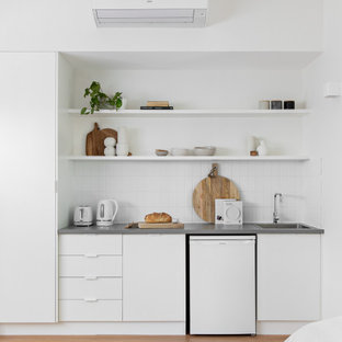 Small contemporary single-wall wet bar in Sydney with a drop-in sink, flat-panel cabinets, white cabinets, white splashback, light hardwood floors, beige floor and grey benchtop.