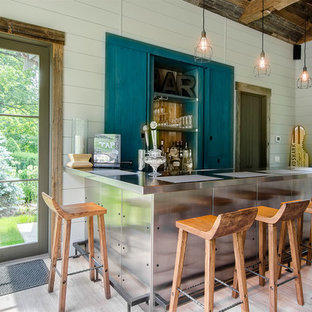 Large country l-shaped light wood floor seated home bar photo in New York with blue cabinets, stainless steel countertops, white backsplash and furniture-like cabinets