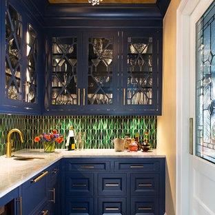 ニューヨークのトラディショナルスタイルのおしゃれなホームバー (L型、アンダーカウンターシンク、落し込みパネル扉のキャビネット、青いキャビネット、緑のキッチンパネル、濃色無垢フローリング、茶色い床、白いキッチンカウンター) の写真
