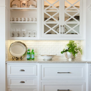 Medium sized nautical single-wall home bar in Orange County with recessed-panel cabinets, white cabinets, medium hardwood flooring, white splashback, no sink, engineered stone countertops and brown floors.