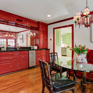 Mid-sized elegant l-shaped medium tone wood floor seated home bar photo in Houston with a drop-in sink, raised-panel cabinets, red cabinets, granite countertops, black backsplash and stone slab backsplash