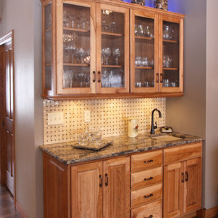 Photo of a small classic single-wall wet bar in Minneapolis with a submerged sink, raised-panel cabinets, medium wood cabinets, engineered stone countertops, beige splashback, mosaic tiled splashback and light hardwood flooring.
