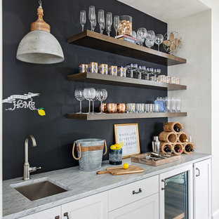 Inspiration for a beach style single-wall medium tone wood floor and brown floor wet bar remodel in Charleston with an undermount sink, white cabinets, blue backsplash and gray countertops