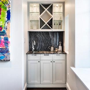 ニューヨークの小さいトランジショナルスタイルのおしゃれなウェット バー (シェーカースタイル扉のキャビネット、白いキャビネット、濃色無垢フローリング、I型、アンダーカウンターシンク、御影石カウンター、黒いキッチンパネル、石スラブのキッチンパネル) の写真