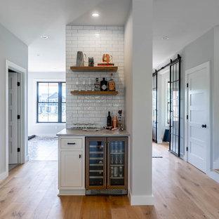 Diseño de bar en casa lineal, campestre, pequeño, sin pila, con armarios estilo shaker, puertas de armario blancas, salpicadero blanco, salpicadero de azulejos tipo metro, suelo de madera clara, suelo beige y encimeras grises