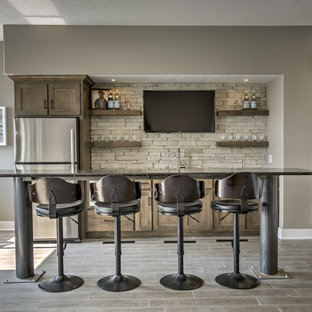 Inspiration for a large classic single-wall breakfast bar in Omaha with a submerged sink, shaker cabinets, dark wood cabinets, beige splashback, stone tiled splashback and grey floors.