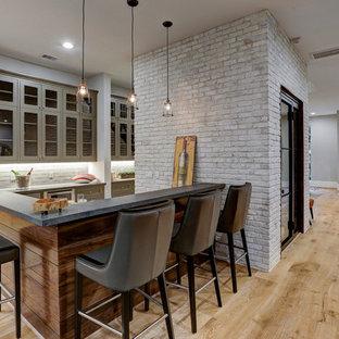 ヒューストンの中くらいのコンテンポラリースタイルのおしゃれな着席型バー (I型、ガラス扉のキャビネット、グレーのキャビネット、グレーのキッチンパネル、サブウェイタイルのキッチンパネル、合板フローリング、ベージュの床、グレーのキッチンカウンター) の写真