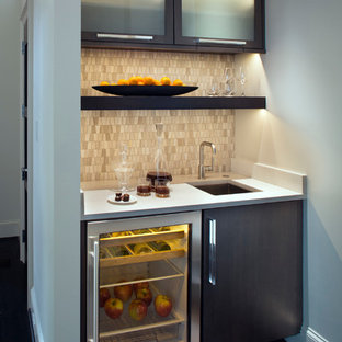 Photo of a small contemporary single-wall wet bar in Other with a submerged sink, glass-front cabinets, dark wood cabinets, engineered stone countertops, grey splashback, stone tiled splashback and dark hardwood flooring.