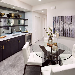 This is an example of a medium sized traditional single-wall wet bar in Calgary with carpet, a submerged sink, shaker cabinets, dark wood cabinets, marble worktops, mirror splashback and grey floors.