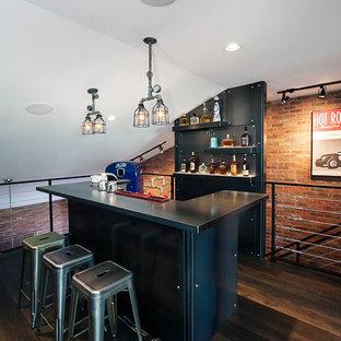 Ejemplo de bar en casa con barra de bar urbano con puertas de armario negras y suelo de madera oscura