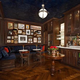 Immagine di un ampio bancone bar classico con ante con riquadro incassato, ante in legno bruno, pavimento in legno massello medio, lavello sottopiano, top in marmo, top multicolore e pavimento marrone