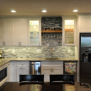 Large cottage chic l-shaped limestone floor and brown floor wet bar photo in Minneapolis with an undermount sink, shaker cabinets, white cabinets, granite countertops, gray backsplash, stone tile backsplash and multicolored countertops