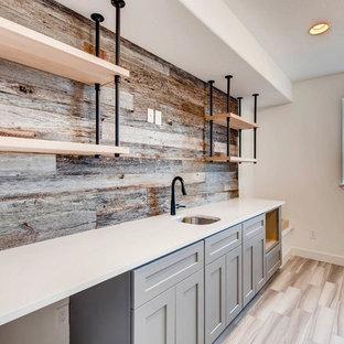 デンバーの中くらいのトランジショナルスタイルのおしゃれなウェット バー (ll型、アンダーカウンターシンク、シェーカースタイル扉のキャビネット、グレーのキャビネット、クオーツストーンカウンター、茶色いキッチンパネル、木材のキッチンパネル、無垢フローリング、茶色い床、白いキッチンカウンター) の写真