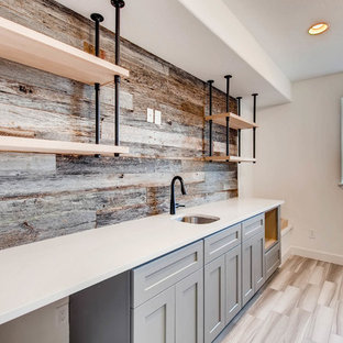 Mid-sized transitional galley medium tone wood floor and brown floor wet bar photo in Denver with an undermount sink, shaker cabinets, gray cabinets, quartz countertops, brown backsplash, wood backsplash and white countertops