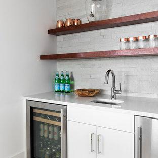 ニューヨークの中くらいのビーチスタイルのおしゃれなウェット バー (I型、アンダーカウンターシンク、フラットパネル扉のキャビネット、白いキャビネット、珪岩カウンター、グレーのキッチンパネル、ライムストーンのキッチンパネル、淡色無垢フローリング、ベージュの床、白いキッチンカウンター) の写真
